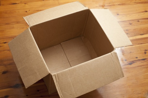 High Angle View of Empty Cardboard Box with Open Flaps on Shiny Hardwood Floor - Moving or Shipping Concept Image